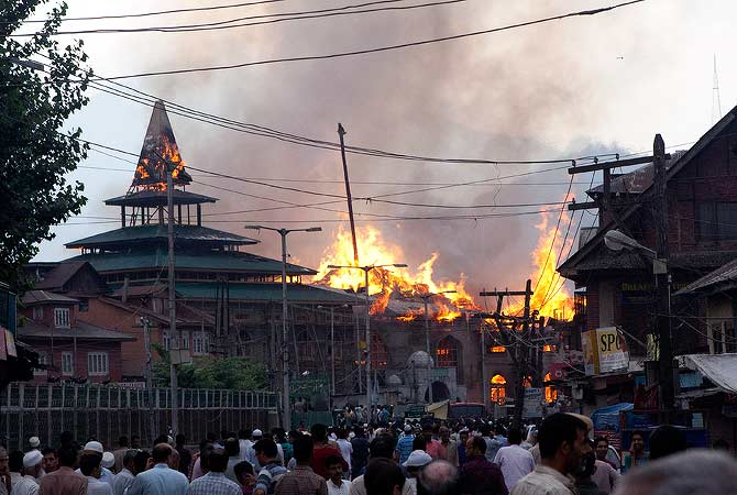 Kashmiri residents watch as firefighters try to extinguish the fire at a nearly 200-years-old shrine of Sheikh Abdul Qadir Jeelani, popularly known as Ghaus-e-Azam, or Dastgeer Sahab, in downtown Srinagar, India, Monday, May 25, 2012. — AP Photo