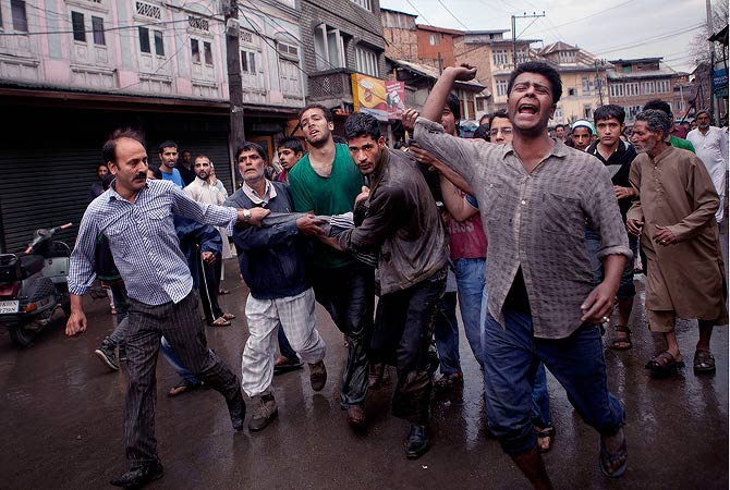 Kashmiri residents chant anti-India slogans as they carry a wounded man for treatment after a fire broke out at the nearly 200-years-old Sheikh Abdul Qadir Jeelani Shrine, popularly known as Ghaus-e-Azam, or Dastgeer Sahab, in downtown Srinagar, India, Monday, May 25, 2012. — AP Photo