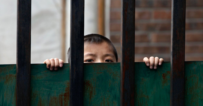 A Chinese boy looks out from the fence of a kindergarten for children.—Reuters Photo