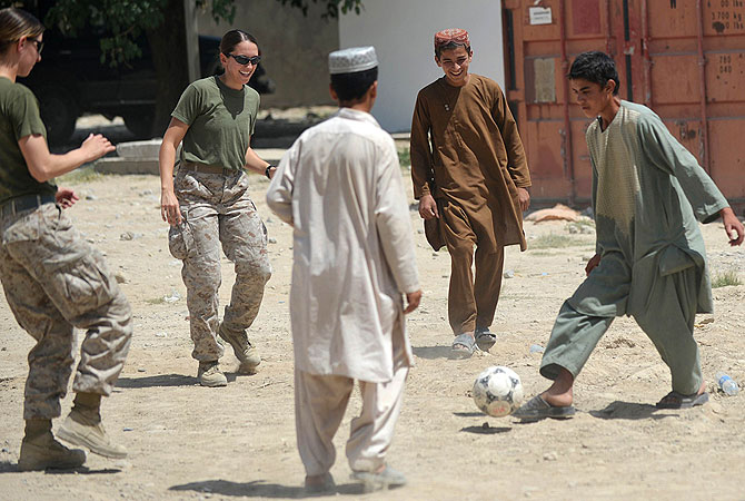 US Marine Cpl. Reagan Odhner (L) assigned in Female Engagement Team (FET) and US Navy Lt. Sarah Pilewski (2L) from 1st Battalion 7th Marines Regiment play football with Afghan children at Forward Operating Base (FOB) Jackson also known as Sabit Khadam. -Photo by AFP