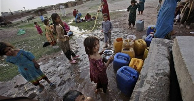 Afghan refugees collect water from a water point in a slum area on the outskirts of Islamabad.—AP Photo