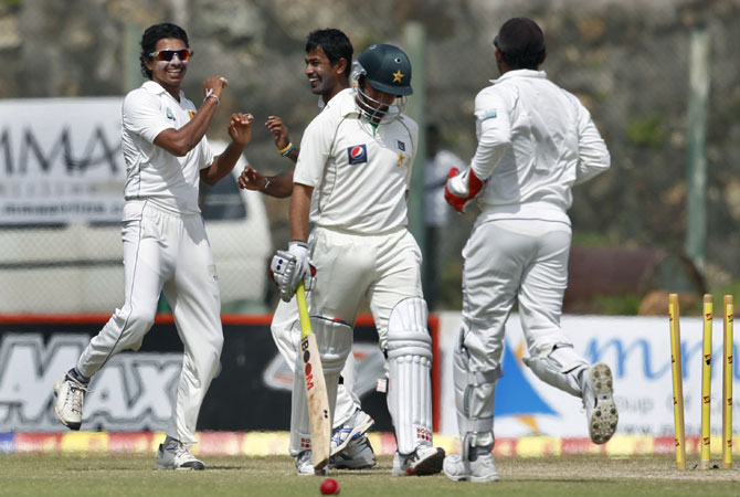 Sri Lanka's Suraj Randiv, left celebrates the dismissal of Pakistan's batsman Saeed Ajmal, second right with Nuwan Kulasekara, second left. -Photo by AP