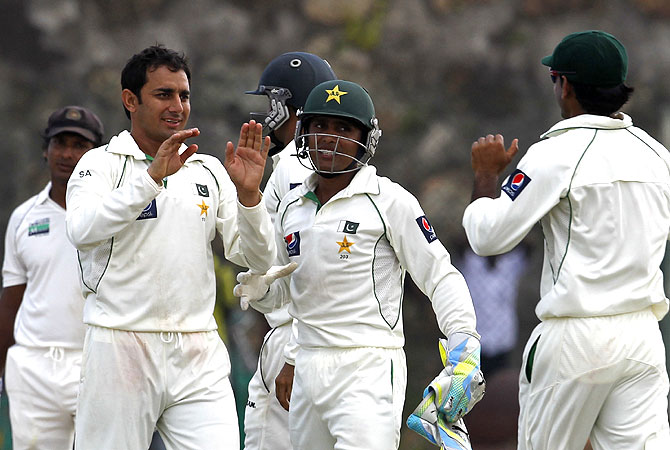 Ajmal (2L) celebrates with teammates after the dismissal of Sri Lanka cricketer Tillakaratne Dilshan (R). -Photo by AP