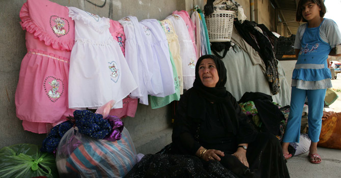Amina Osman (C) sells second hand clothes in the city of Arbil.—AFP Photo