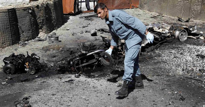 An Afghan policeman removes evidence from the site of a suicide bomb attack.—Reuters Photo