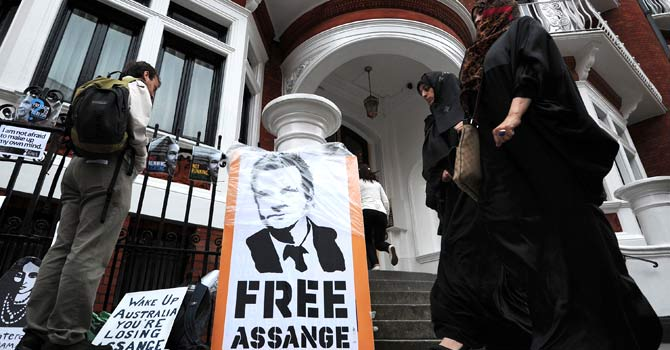 Women walk past protest placards outside the Ecuadorian embassy in London, on June 23, 2012, where supporters of Wikileaks founder Julian Assange gathered to demonstrate. Ecuador today recalled its ambassador to Britain to discuss what to do about WikiLeaks founder Julian Assange, who has sought refuge in their diplomatic mission in London. Assange, an Australian national, sought refuge in the Ecuadoran embassy on June 19 and asked Quito to give him asylum as he seeks to avoid extradition to Sweden on allegations of rape, fearing Stockholm will turn him over to the United States. – Photo by AFP