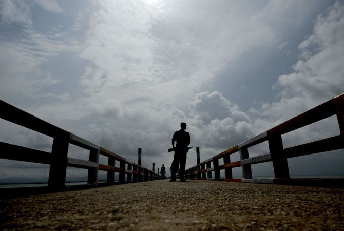 A Bangladeshi Border Guard keeps watch on a jetty on the Naf river in Teknaf. Bangladesh refused three more boatloads of Rohingya Muslims fleeing sectarian violence in Myanmar, officials said, despite growing calls for the border to be opened. -Photo by AFP