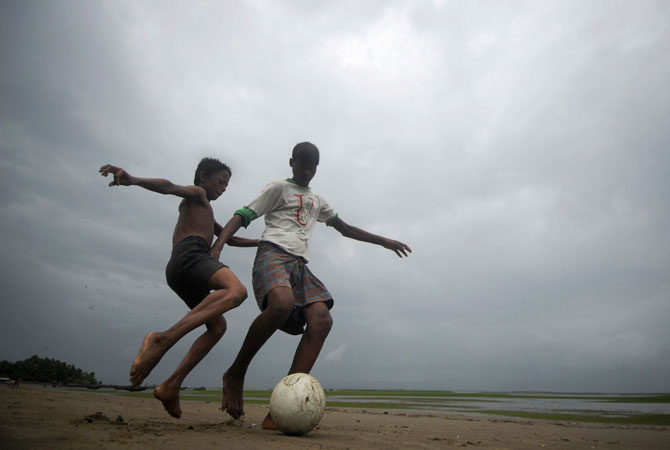 Bangladeshi children play football beside the Naf river in Teknaf. -Photo by AFP
