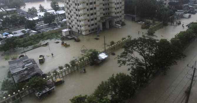 A street is seen submerged by flood water in Chittagong June 26, 2012. At least six people have died by different landslides in Chittagong and Cox's Bazar as heavy rainfall submerged the port city, local media reported. REUTERS