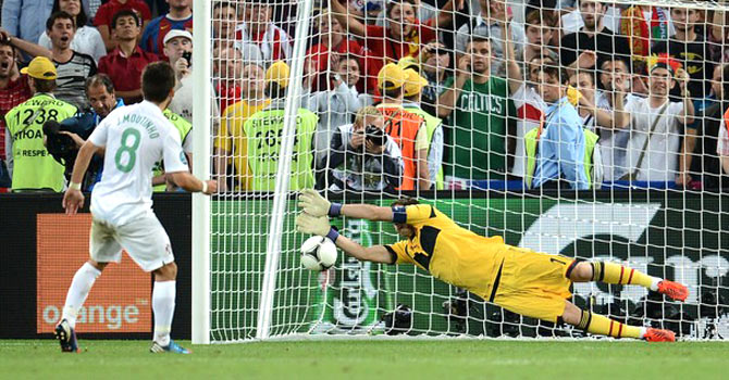 Spanish captian Iker Casillas saves Portugal midfielder Moutinho's penalty kick. - Photo by AFP