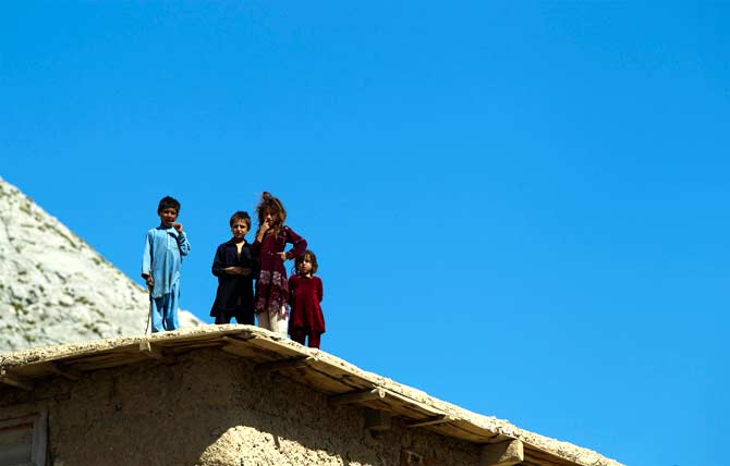 Afghan children stand on a rooftop to watch soldiers from 3rd Platoon, Dagger Company of the 2nd Battalion, 12th Infantry Regiment during a patrol through the village of Sandray in the Pech River Valley of Afghanistan's Kunar Province. ? Photo by AFP