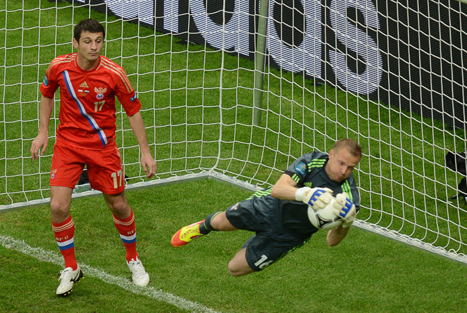Russian goalkeeper Vyacheslav Malafeev grabs the ball next to Russian midfielder Alan Dzagoev.