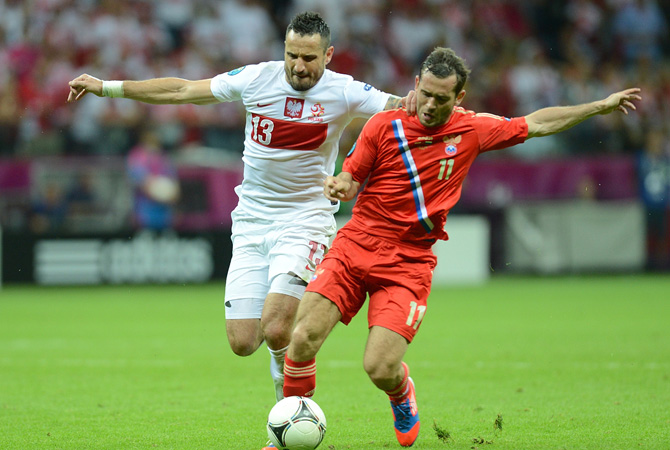 Polish defender Marcin Wasilewski vies with Russian forward Aleksander Kerzhakov during  the Euro 2012 championships football match Poland vs Russia at the National Stadium in Warsaw.