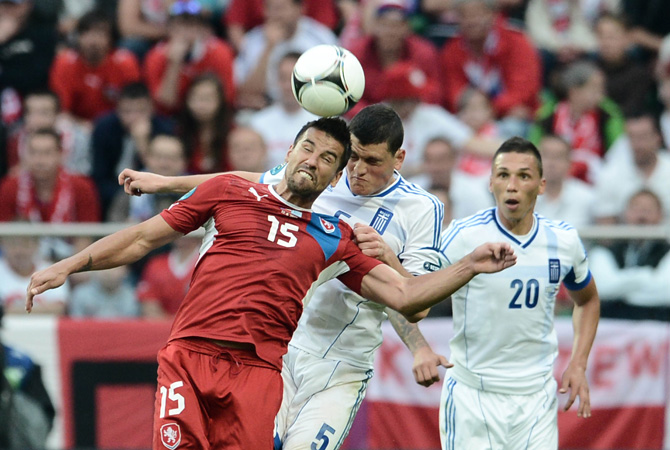 Czech forward Milan Baros and Greek defender Kyriakos Papadopoulos head the ball during the Euro 2012 championships football match Greece vs Czech Republic at the Municipal Stadium in Wroclaw.