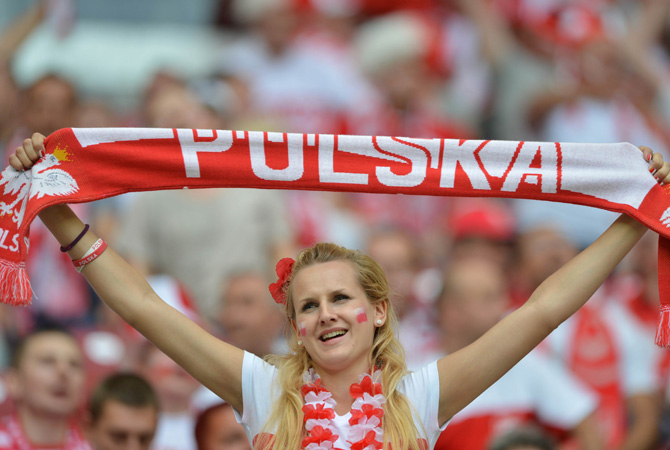 A  Polish supporter holds her team banner.