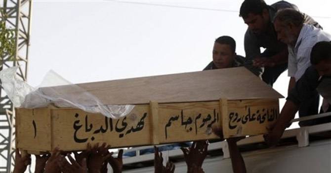 Family members of a boy who was killed in a car bomb attack load his coffin onto a vehicle.—AP Photo