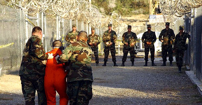 "A detainee at Guantanamo Bay is dragged by officials. While some versions of the truth may be revealed through court proceedings, the government has ensured that it will control the flow of information by asserting that all pertinent documents to the defence of Guantanamo detainees are ""classified."" — File photo by Reuters"