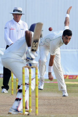 Umar Gul (R) toils hard in the hot conditions. -Photo by AFP
