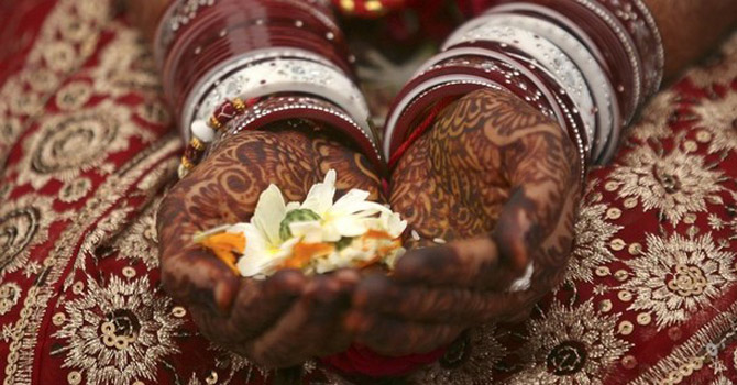 A Hindu bride holding flowers in her hands.—Reuters Photo