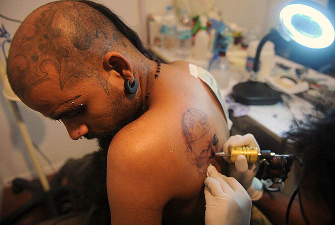 Indian tattoo enthusiast Moses gets a design inked on his body at a tattoo convention in Mumbai. The event is a showcase of tattoo art which has for centuries been used in India for religious symbolism but  is now emerging as a fashion statement amongst the young and trendy urban youth. -Photo by AFP