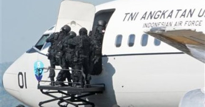 Indonesia military special force personnel storm into a plane.—AP Photo