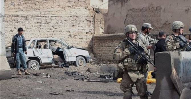 Isaf are seen at the scene of a suicide attack with Afghan security forces in Afghanistan.—AP Photo
