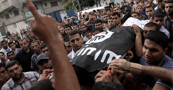 Palestinians carry the body of militant Basel Ahmed during his funeral in al-Bureij refugee camp in the central Gaza Strip on June 22, 2012 after he was killed and two were wounded, one seriously, when Israeli warplanes struck east of Al-Bureij. AFP