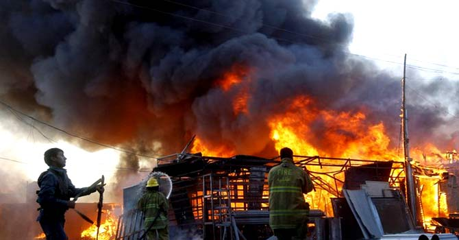 Rescue officials try to extinguish fire at a commercial market in Jalalabad. — File photo by Reuters