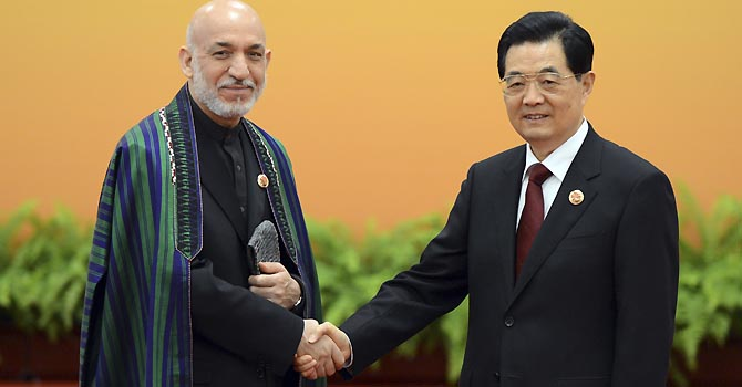 Chinese President Hu Jintao, right, and Afghan President Hamid Karzai pose for photos before their meeting at the Shanghai Cooperation Organization (SCO) summit in the Great Hall of the People in Beijing, Thursday, June 7, 2012. (AP Photo/Mark Ralston, Pool)