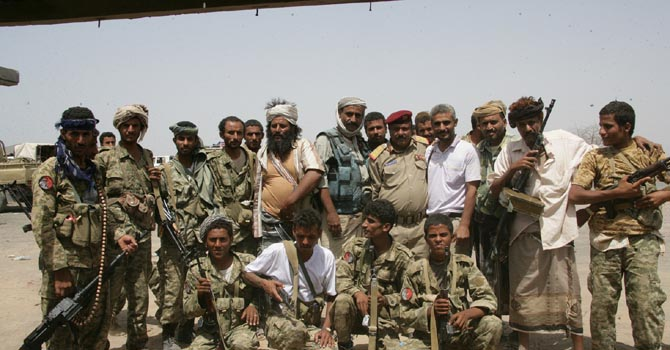 In this handout photo provided by the Defense Ministry, Yemeni army soldiers and tribesmen loyal to the army pose for a group photo at their position near the city of Zinjibar, Yemen, Tuesday, June 12, 2012. Yemeni troops backed by armed tribesmen routed al-Qaida on Tuesday from two southern strongholds the terror network had held for more than a year, the most significant victory so far in a monthlong offensive against a local franchise that has tried time and again to bomb U.S.-bound planes. (AP Photo/Yemen Defense Ministry)