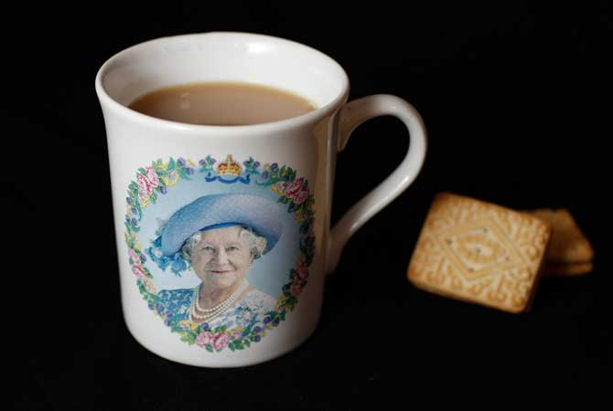 A cup of tea with two custard cream biscuits