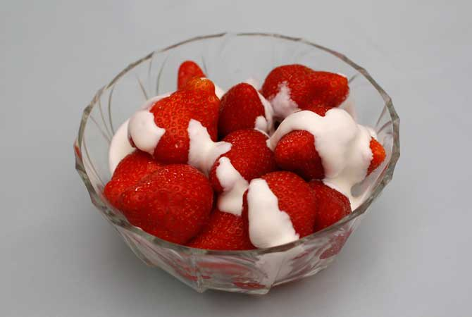 A traditional British desert of a bowl of strawberries and cream
