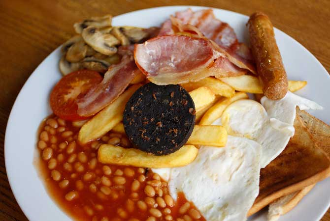 A traditional full English breakfast of sausages, chips, baked beans, bacon, black pudding and toast is pictured at 'Enough To Feed an Elephant' cafe in London
