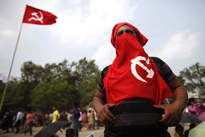 A supporter of establishment faction of the Unified Communist Party of Nepal (Maoist) listen to the speech given by the party leaders during the mass rally in Kathmandu, Nepal. -Photo by AP