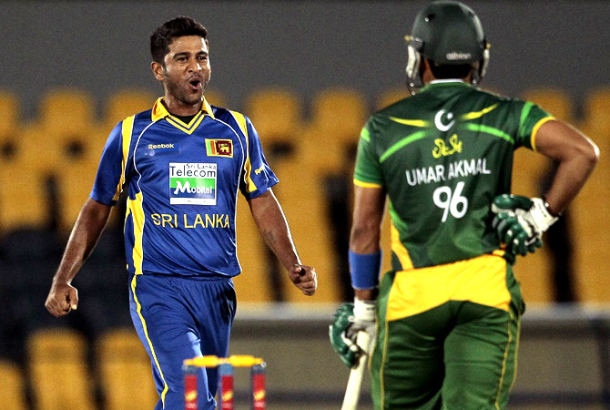 Sri Lankan bowler Kaushal Lokuarachchi, left, celebrates the dismissal of Pakistan's batsman Umar Akmal. -Photo by AP