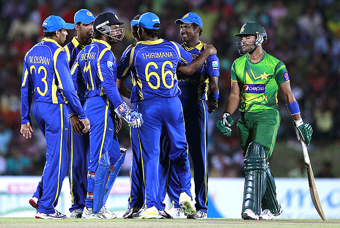 Pakistan's Umar Akmal walks off the field after his dismissal as Sri Lanka's team celebrate. -Photo by Reuters