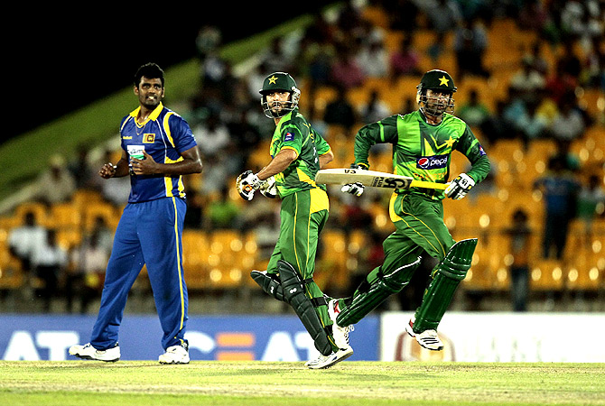 Pakistan's batsmen Shoaib Malik , right, and Shahid Afridi run between wickets as Sri Lankan bowler Thisara Perera , left, looks on. -Photo by AP