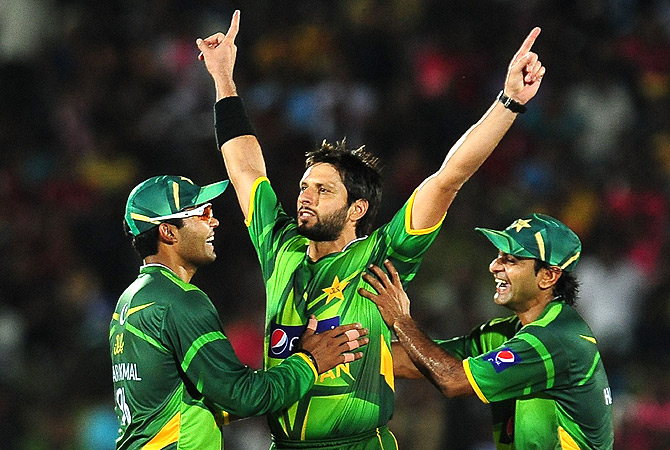 Pakistan cricketer Shahid Afridi (C) celebrates with teammates captain Mohammad Hafeez (R) and Umar Akmal (L) after he dismissed Sri Lankan cricketer Tillakaratne Dilshan