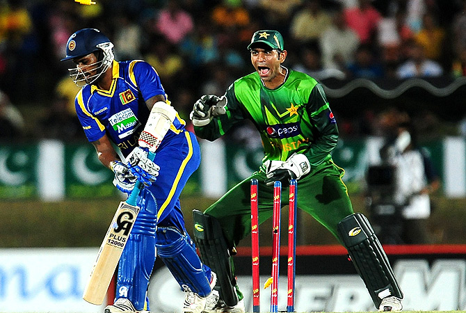 Sri Lankan cricketer Chamara Kapugedera (L) gets dismissed by unseen Pakistan cricketer Shahid Afridi as wicketkeeper Shakeel Ansar looks on. -Photo by AFP