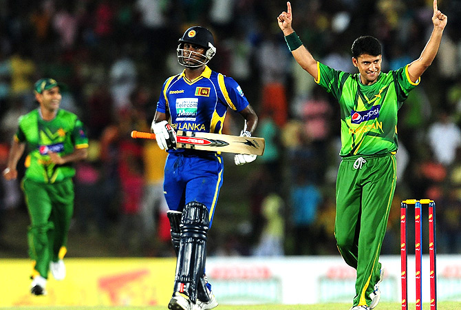 Pakistan cricketer Yasir Arafat (R) celebrates after dismissing Sri Lankan cricketer  Angelo Mathews. -Photo by AFP
