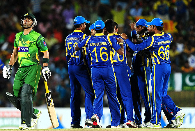 Pakistan cricketer Ahmed Shehzad (L) reacts after being dismissed. -Photo by AFP