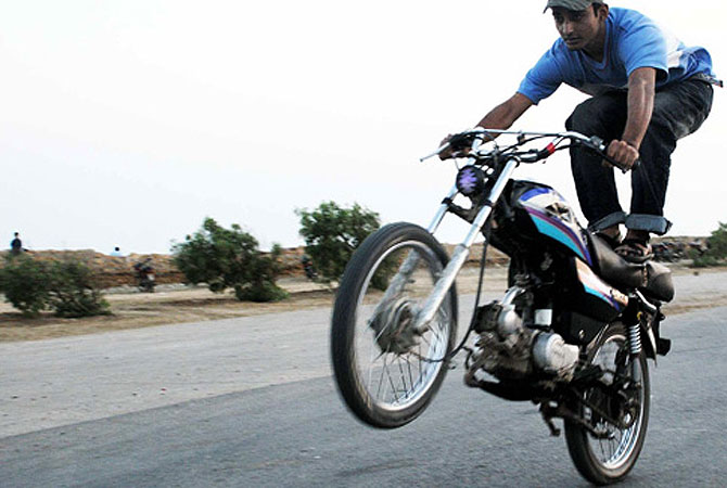 A young man performs impromptu bike stunts at a deserted road in Karachi, Pakistan.