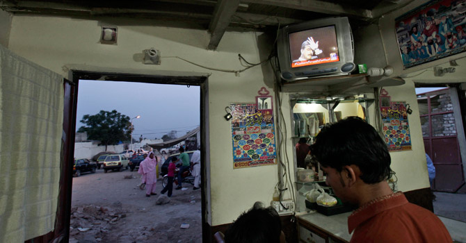 A TV broadcast showing Yousuf Raza Gilani at a barber shop in a neighbourhood, in Islamabad.—AP Photo