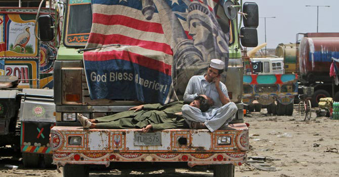 A man speaks on his mobile phone while another rests his head on his lap on the bumper of an oil tanker used to transport Nato fuel supplies to neighbouring Afghanistan in Karachi.—AP Photo