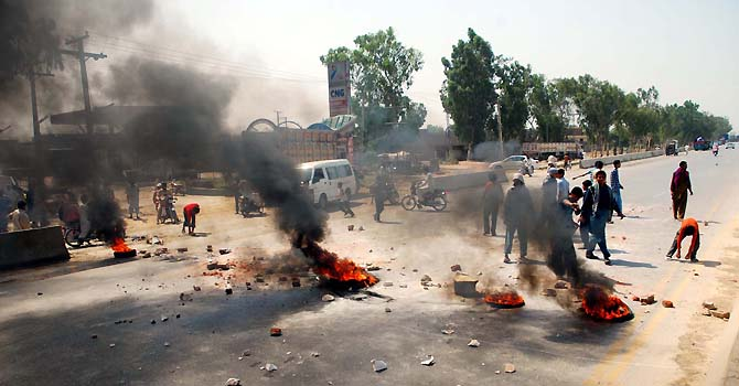 An angry protester burns tyres on GT.road during  protest demonstration residents of Gujranwala against electricity load-shedding on Sunday, June  17, 2012. (Zameer Rizvi/PPI Images).