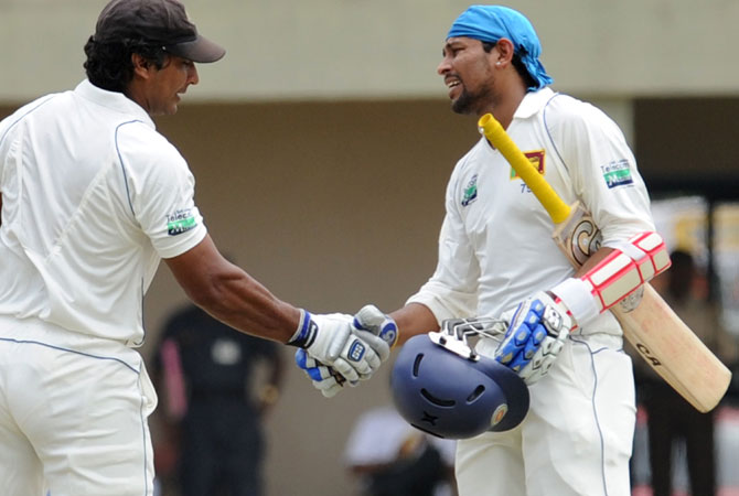 Tillakaratne Dilshan (R) is congratulated by teammate Kumar Sangakkara (L) after scoring a half-century. -Photo by AFP