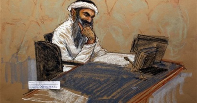 In this photo of a sketch Khalid Sheikh Mohammed reads a document during his military hearing at the Guantanamo Bay.—AP Photo