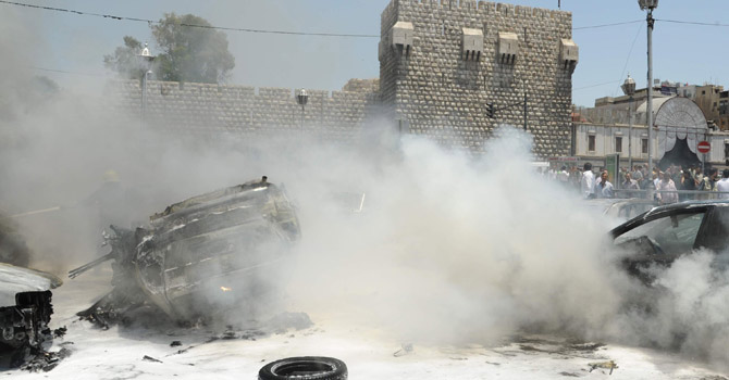 Smoke fills the air at the scene of two huge bomb explosions outside the Palace of Justice in Central Damascus.—AFP Photo