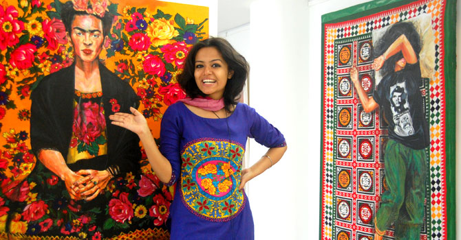 Artist Summaiya Jillani with some of her art, including her take on Frida Kahlo at an exhibition – Photo by Salman Jillani /Hosh Media