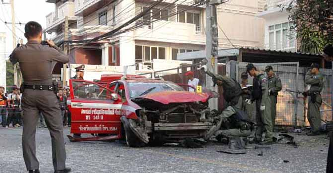 Policemen inspect a taxi damaged in an explosion in Ekamai area in central Bangkok February 14, 2012.
